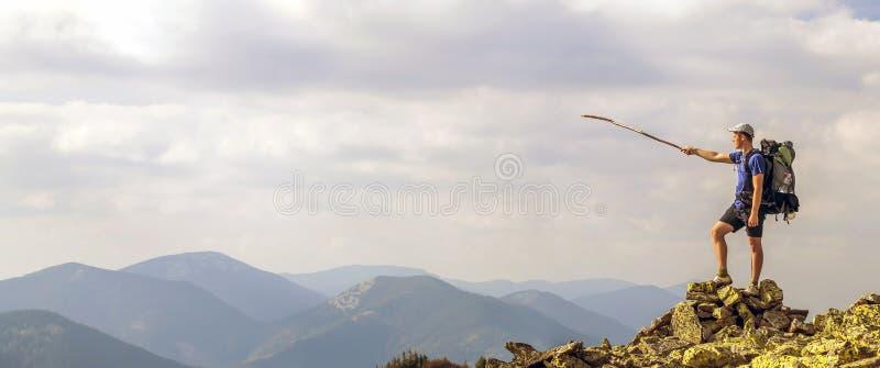 Mann auf Spitze des Berges Emotionale Szene Junger Mann mit backpac lizenzfreie stockfotos