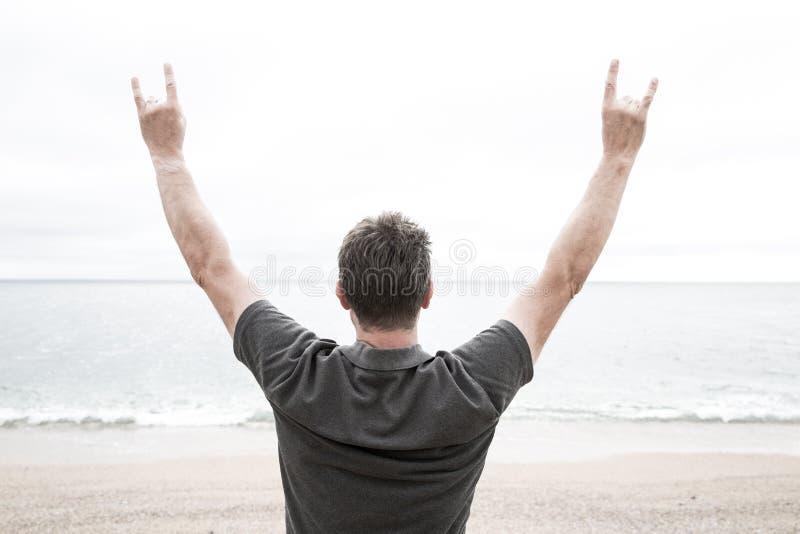 Mann auf Strand mit den Armen, die in Hörner angehoben werden, gestikulieren stockbilder