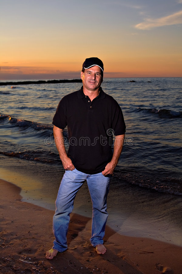 Mann auf Strand-Sonnenuntergang stockfoto
