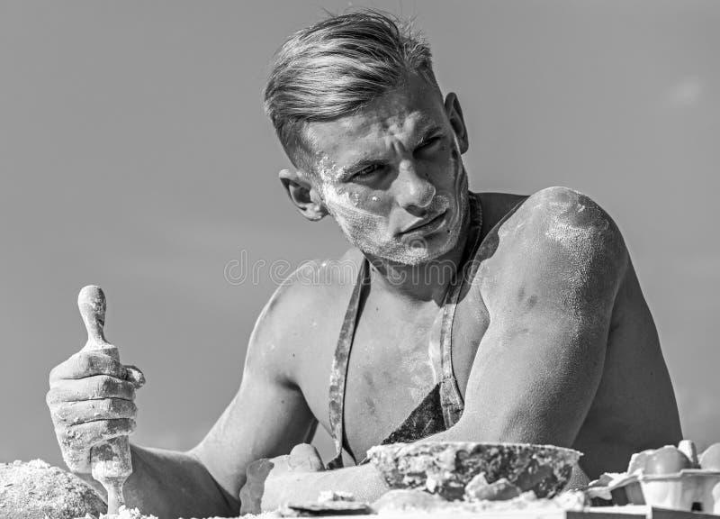 Mann auf strengem Gesicht mit dem blonden Haar trägt Schutzblech, Himmel auf Hintergrund Chefkonzept Kochen Sie mit dem Torso häl lizenzfreie stockfotos