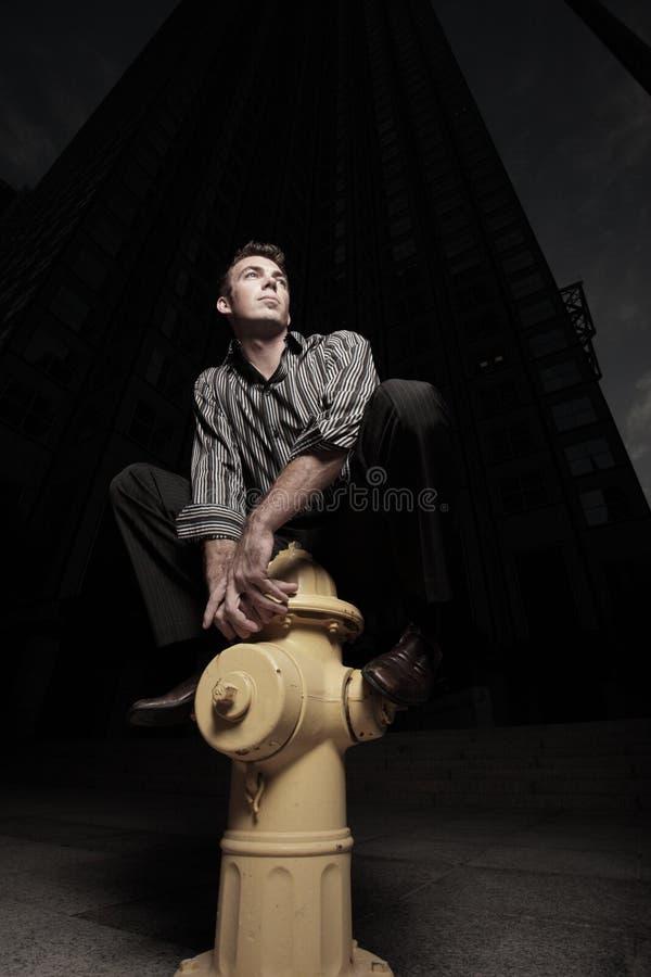 Mann aufgeworfen auf einem Feuerhydranten stockfoto
