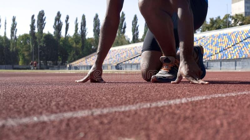 Mann in Ausgangsposition auf Bahn, Berufsläufertraining am Stadion stockbild