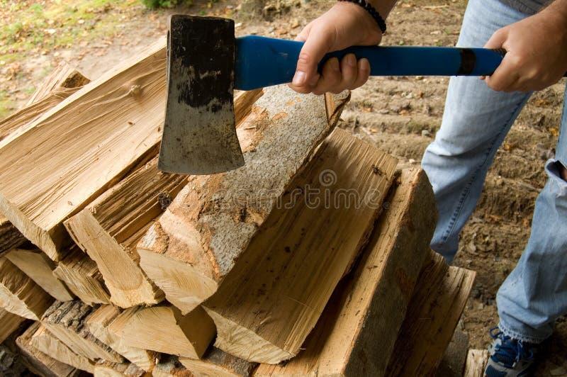Mann-Ausschnitt-Brennholz mit einer blauen Axt lizenzfreies stockbild