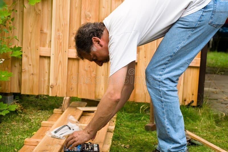 Mann bauen einen hölzernen Zaun auf stockfotos