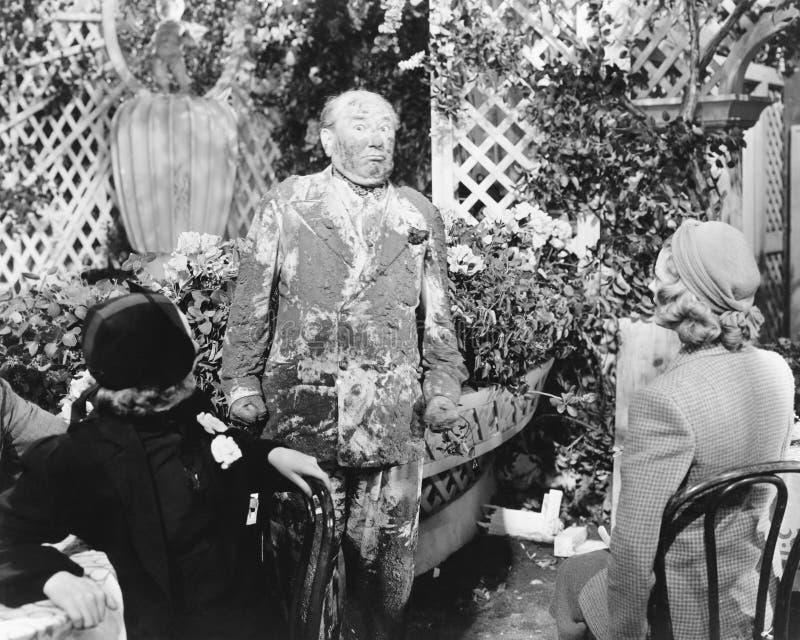 Mann bedeckt im Schlamm, der vor zwei Damen steht (alle dargestellten Personen sind nicht längeres lebendes und kein Zustand exis stockbilder