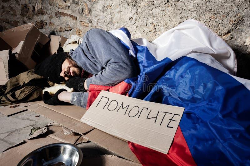 Mann bedeckt mit der russischen Flagge, die auf Straße schläft stockfoto