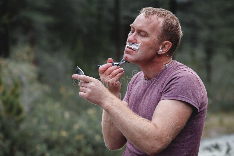 Mann bedeckt, wenn Schaum mit einem Rasiermesser rasiert wird Mann mit unrasiertem Gesicht mit Bergen und Bäumen im Hintergrund D stockfoto