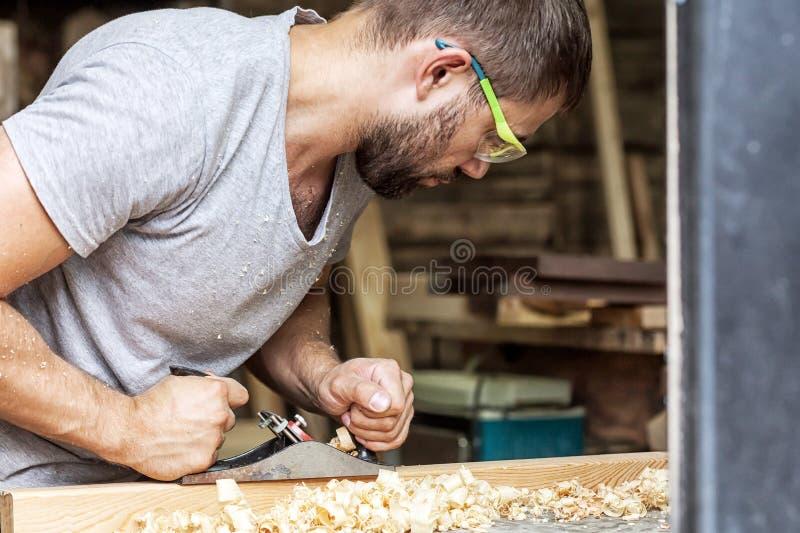 Mann behandelt ein hölzernes mit einer Fläche der schwarzen Steckfassung stockfoto