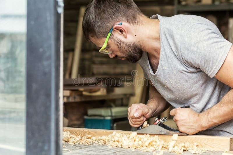Mann behandelt ein hölzernes mit einer Fläche der schwarzen Steckfassung stockbilder