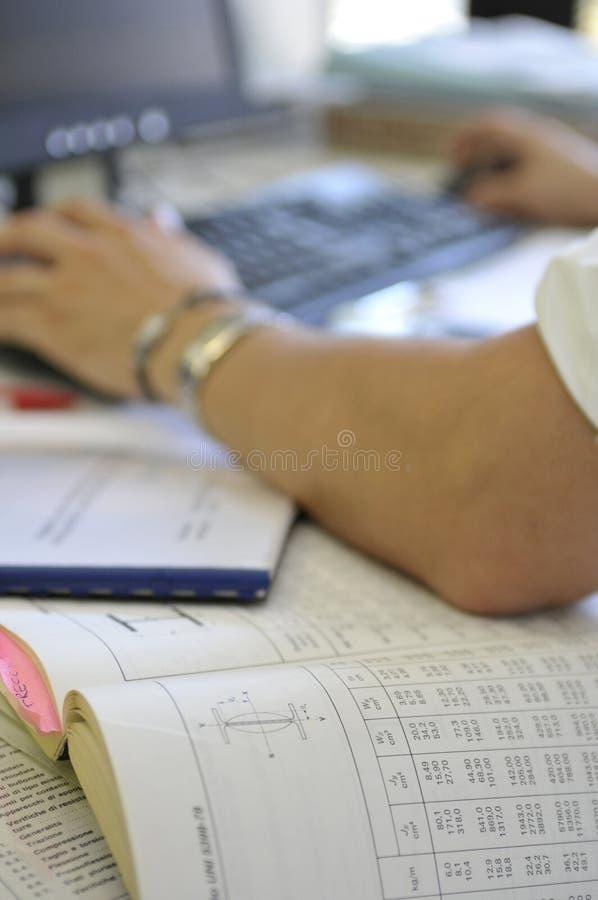 Mann bei der Arbeit über Schreibtisch lizenzfreie stockfotografie
