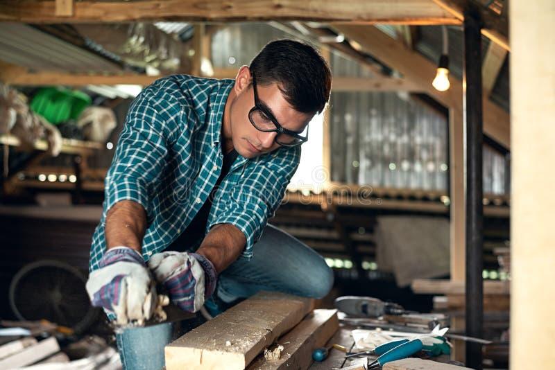 Mann bei manueller Hobelmaschine der Holzverarbeitung in der Hauptwerkstatt, Handarbeit, Haupthandwerker lizenzfreie stockbilder