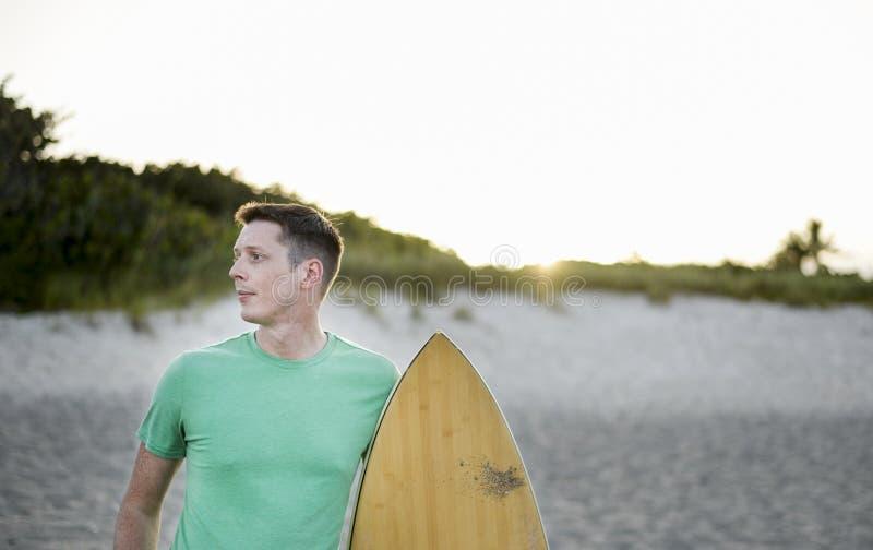 Mann bei Sonnenuntergang mit einem Surfbrett lizenzfreie stockfotografie