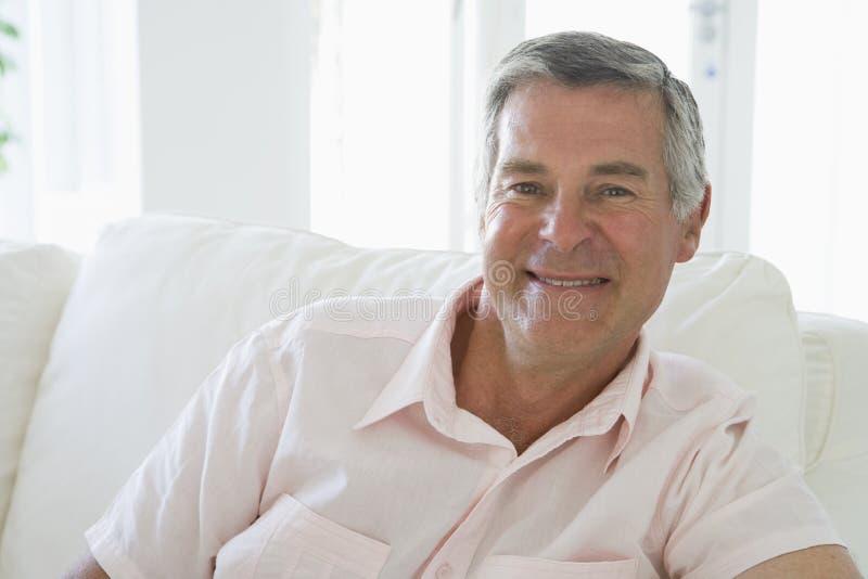 Mann beim Wohnzimmerlächeln stockfoto