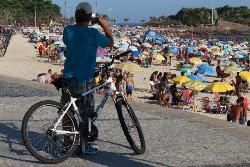 Mann benutzt Smartphone, um die Schönheit des Strandes zu fotografieren lizenzfreie stockbilder