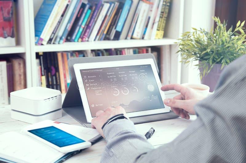 Mann benutzt Tabletten-PC mit persönliche Finanzmanager lizenzfreie stockfotografie
