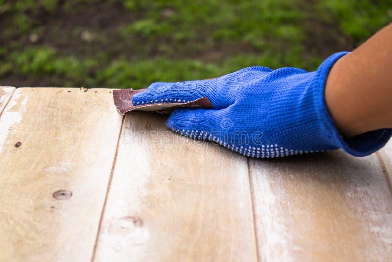 Mann bereitet die Oberfläche für die malenden und reibenden Hände vor stockbild