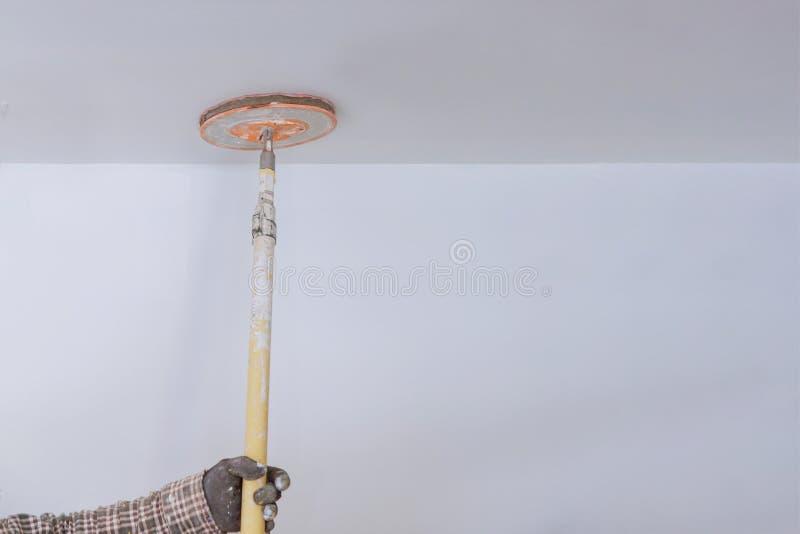 Mann bereitet eine Oberfläche mit einer Sandpapierwartungsreparatur bearbeitet Erneuerung in der Ebene vor wiederherstellung stockfoto