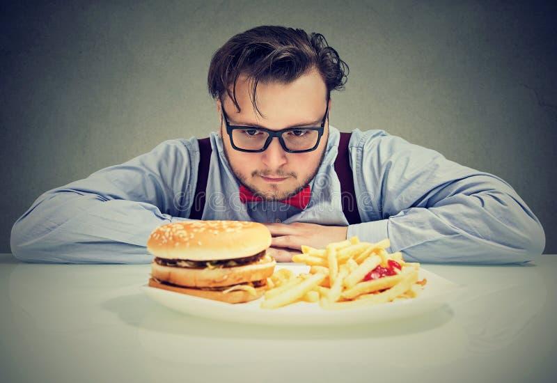 Mann besorgt um ungesunden Schnellimbiß lizenzfreies stockbild