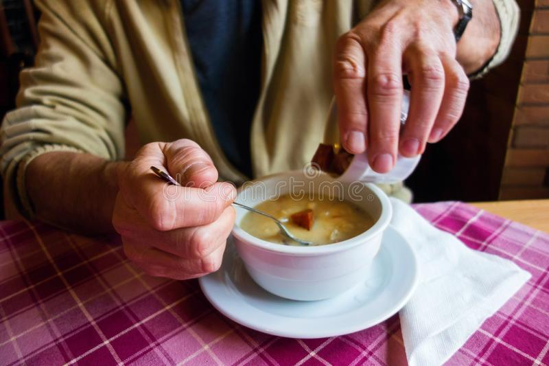 Mann besprüht gezüchtete Würfel in Schüssel mit Suppe lizenzfreies stockbild