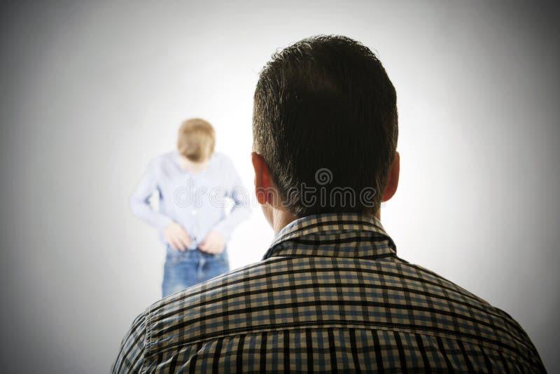 Mann betrachtet den Jungen stockfotografie