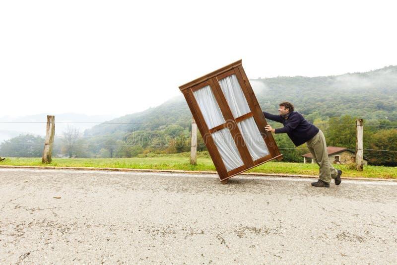 Mann bewegt Kabinette, trifft eine Maßnahme lizenzfreie stockfotos