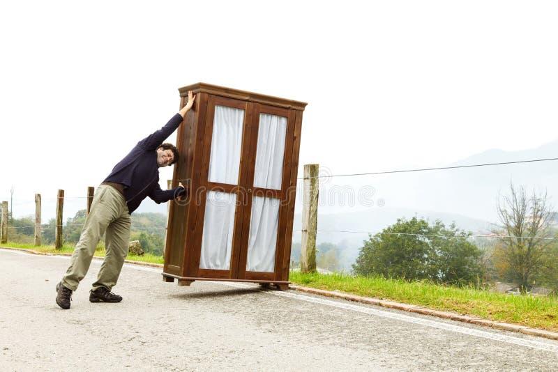 Mann bewegt Kabinette, trifft eine Maßnahme lizenzfreie stockfotografie