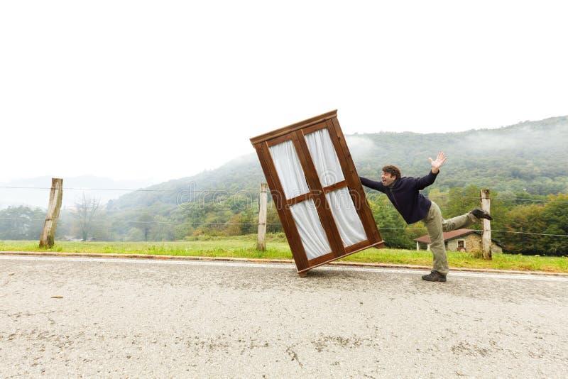 Mann bewegt Kabinette, trifft eine Maßnahme stockbild