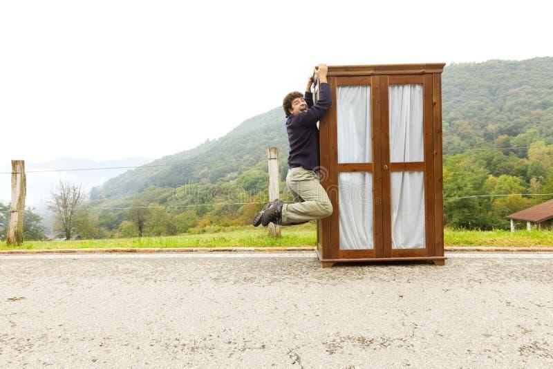 Mann bewegt Kabinette, trifft eine Maßnahme stockfoto