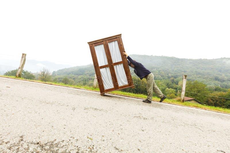 Mann bewegt Kabinette, trifft eine Maßnahme lizenzfreie stockbilder