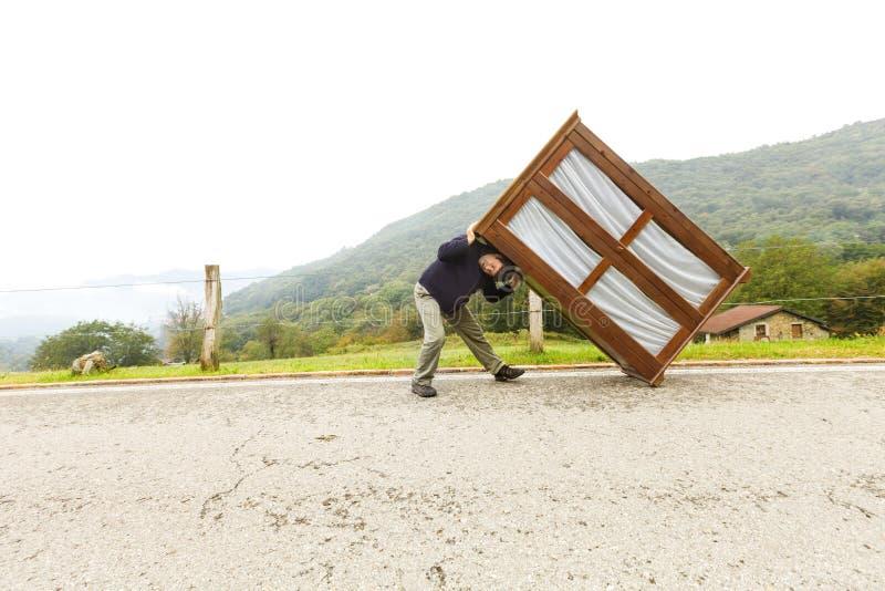 Mann bewegt Kabinette, trifft eine Maßnahme stockfotos
