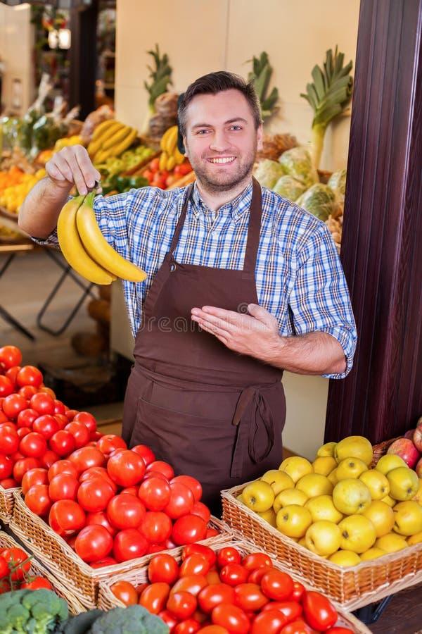 Mann bietet frische Bananen an stockfotografie