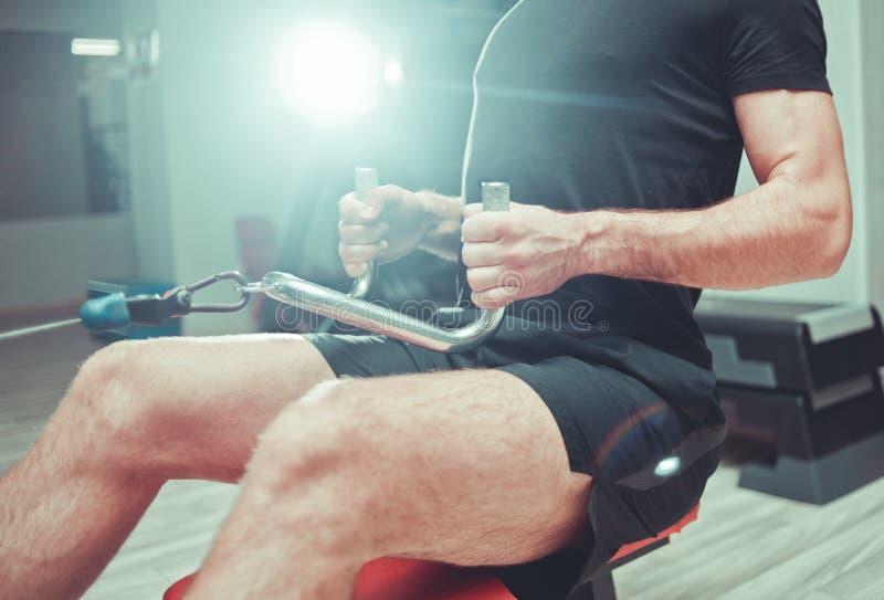 Mann bildet mit Ausrüstungsrudersport-Trainingsmaschine aus stockbilder