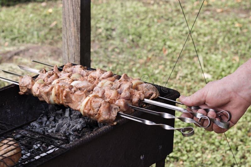 Mann brät Fleisch auf dem Grill, Fleisch auf Aufsteckspindeln und auf heißen Kohlen, ein Picknick in der Natur stockfotografie