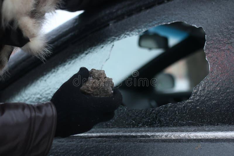 Mann brach das Glas des Autos ein kleiner Stein stockbild