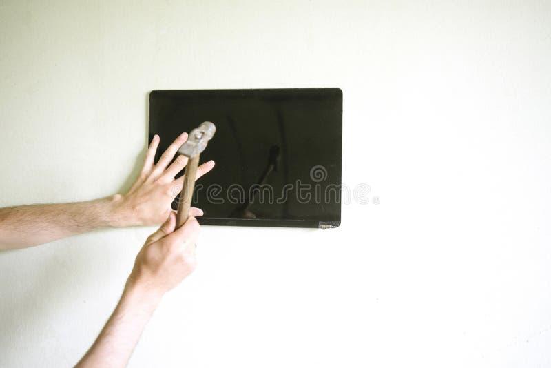 Mann bricht den Bildschirm mit einem Hammer lizenzfreies stockbild