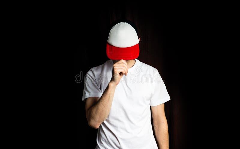 Mann das leere weiße, in roter Baseballmütze und in weißem T-Shirt, auf einem schwarzen Hintergrund, verspotten oben, freier Raum stockbilder