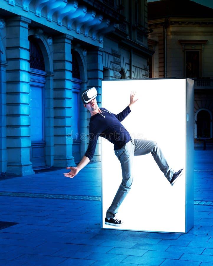 Mann in den Gläsern der virtuellen Realität, die aus ein Straßenplakat herauskommen stockfotografie