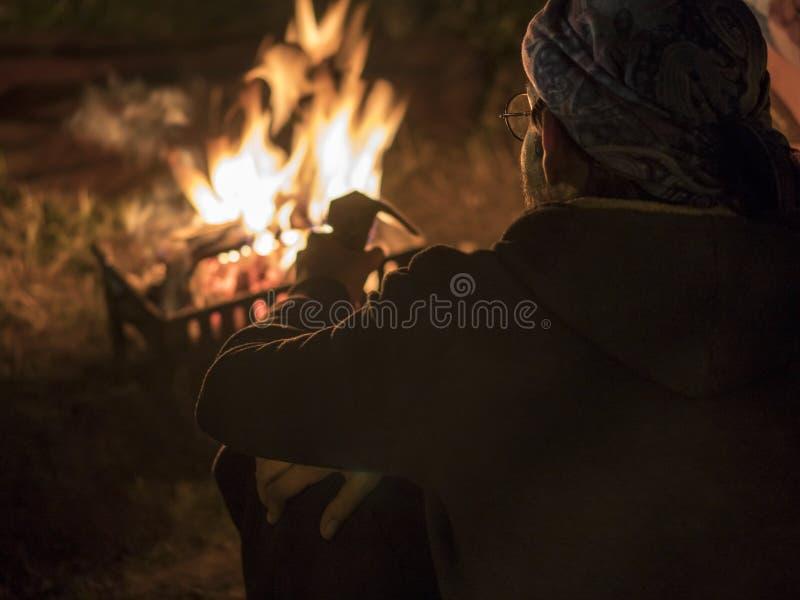 Mann in den Gläsern nahe dem Feuer nachts in altem Höhlen-Stadt Uchisar-Schloss in Cappadocia stockbilder
