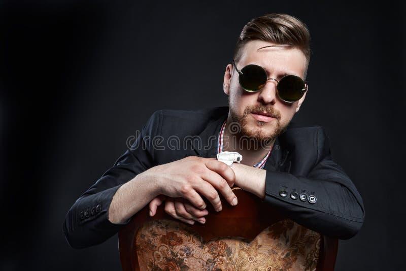Mann in den Gläsern sitzt auf einem Stuhl Überzeugter Mann des Geschäftsmannes SEO Manager, der auf einem schwarzen Hintergrund a stockfoto