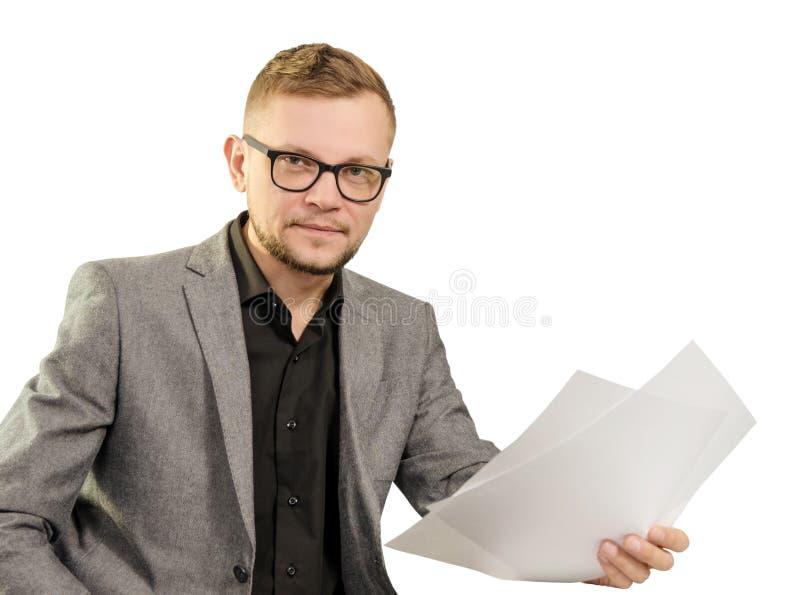 Mann in den Gläsern und in der Jacke mit Dokumenten in seiner Hand lächelnd, um die Kamera zu betrachten lokalisiert auf weißem H lizenzfreie stockfotos