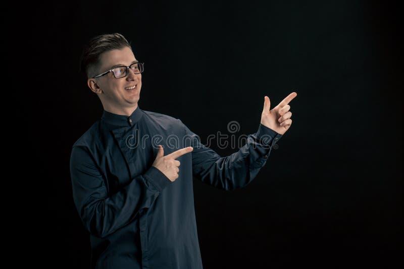 Mann in den Gläsern zeigt mit seinem Finger auf die Seite lizenzfreie stockfotografie