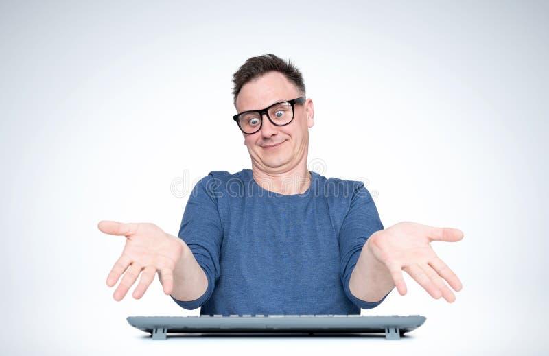 Mann in den Glasarbeiten am Computer, verbreitet er seine Hände in einer Geste, die ich nicht kenne, auf hellem Hintergrund Front stockfotografie