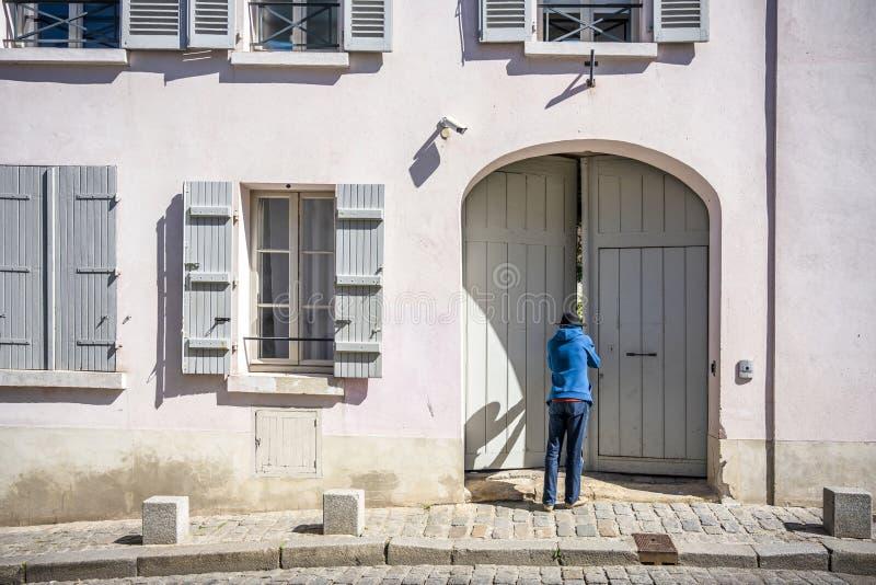 Mann in den Hutgleichen in den Hof des Hauses mit Fensterläden durch etwas offenes Tor lizenzfreies stockbild