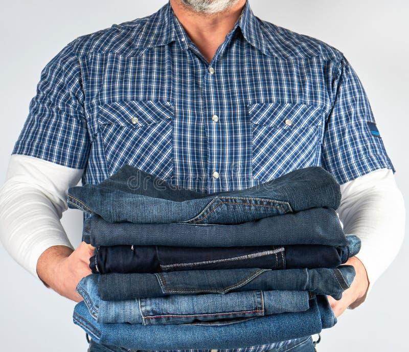 Mann in den Jeans und in blauem kariertem Hemd, die einen Stapel von Jeans halten lizenzfreie stockfotos