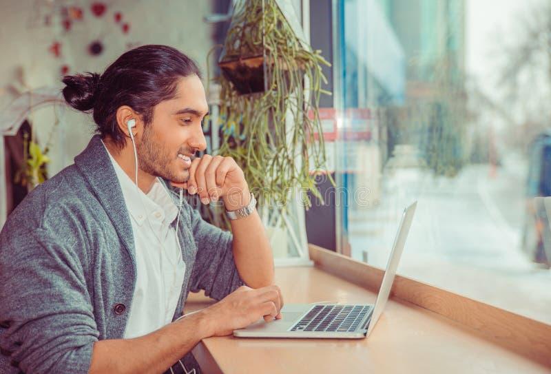 Mann in den Kopfhörern, die das Computerlächeln glücklich betrachten lizenzfreie stockfotografie