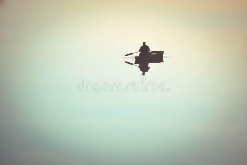 Mann in den Rudern eines Ruderboots im Wasser stockfotografie