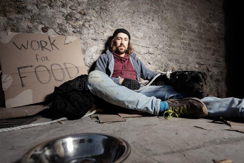 Mann in den schmutzigen Lappen, die Hundesitzen auf Bürgersteig umarmen lizenzfreies stockfoto