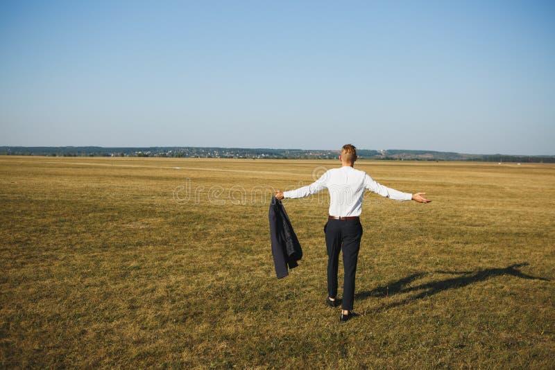 Mann in den schwarzen Hosen und im weißen Hemd mit Jacke in den Händen Es symbolisiert Wahlfreiheit nach Entlassung von der Arbei stockfoto