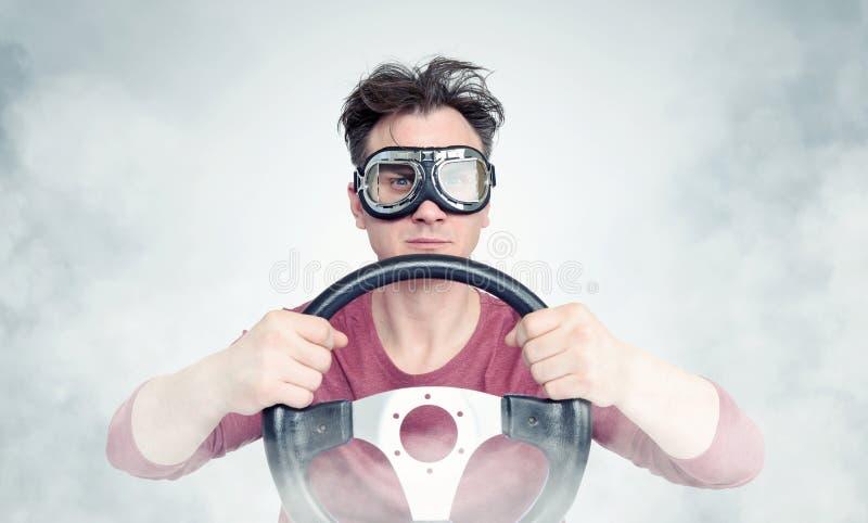 Mann in den stilvollen Schutzbrillen mit Lenkrad auf Hintergrund, Autofahrerkonzept lizenzfreie stockfotos