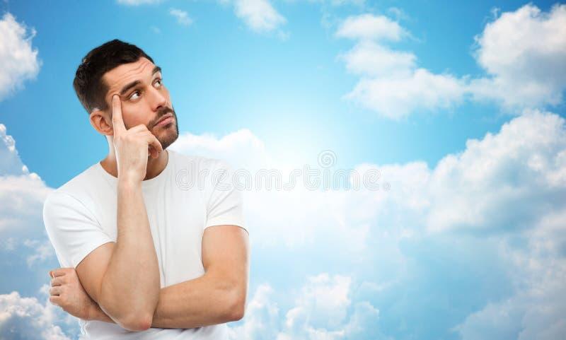 Mann, der über blauem Himmel denkt stockfotos